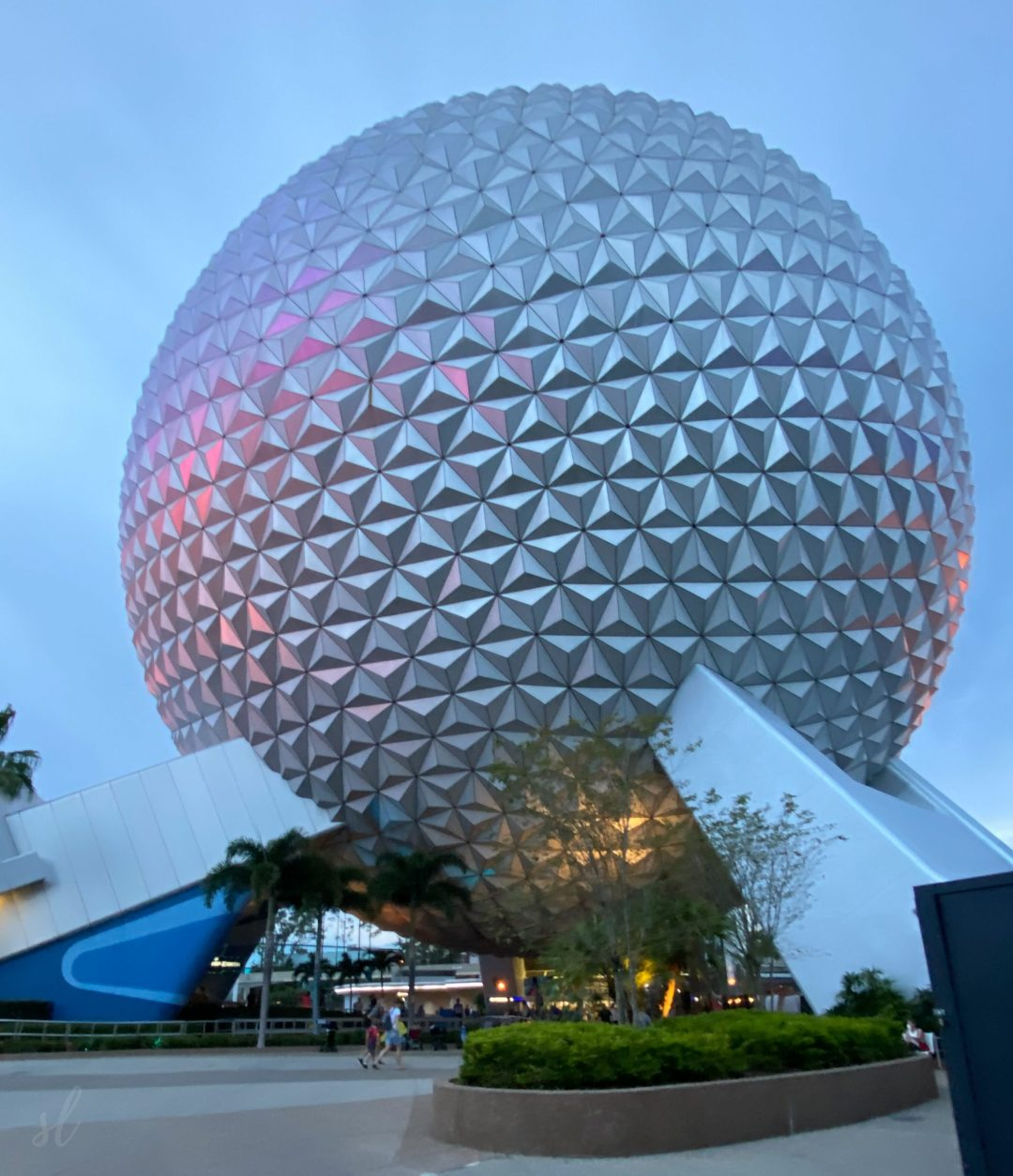 White spherical structure with pink lights reflected on it amidst a dusk backdrop