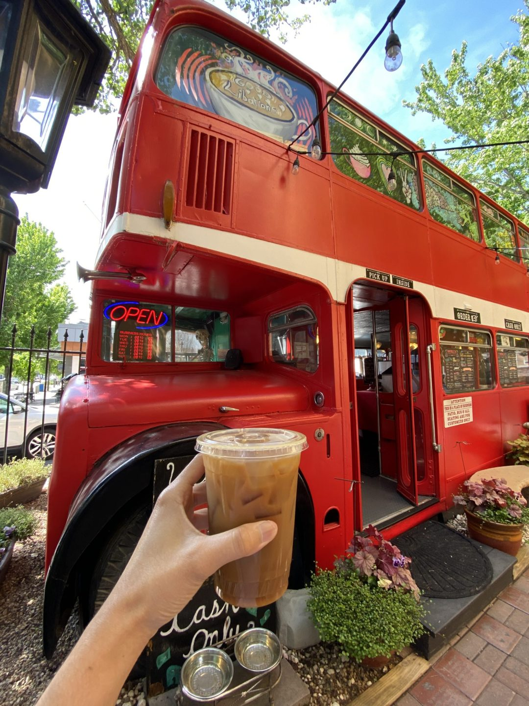 Iced coffee in front of a red double-decker bus