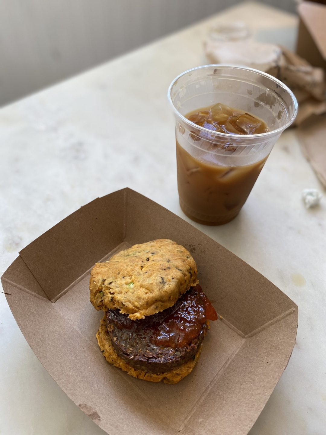 Biscuit with hemp sausage and pepper jelly; iced coffee in the background
