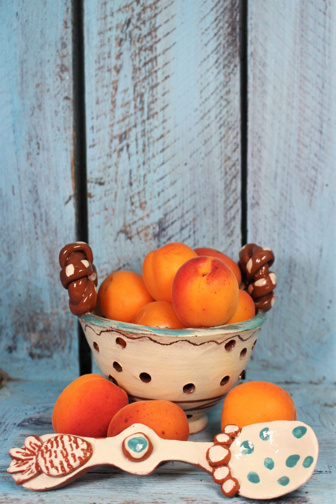 hand thrown slipware colander bowl with fresh peaches plus a slipware pottery spoon oin blue and white