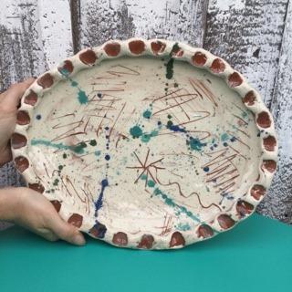 hands holding up a large splatter platter made by sarah monk ceramics