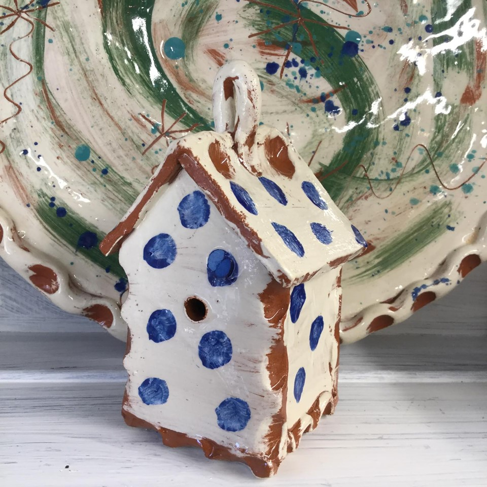 slipware ceramic bug house by sarah monk ceramics in white with cobalt blue dots on a shelf in front of a green plate
