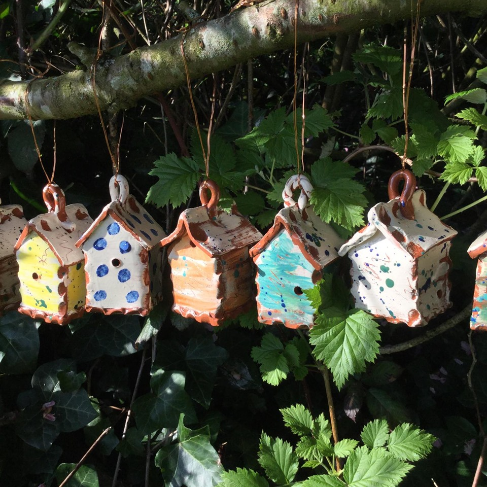 five pottery bug houses hanging on a branch with dappled sunlight