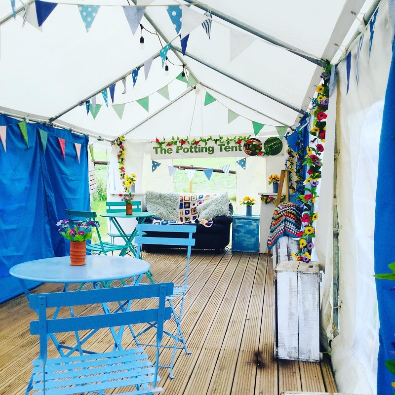 The interior of the potting tent marquee decorated with bunting and bistro tables