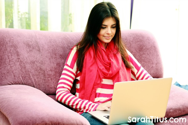 Young smiling woman sitting on the sofa and typing on a laptop