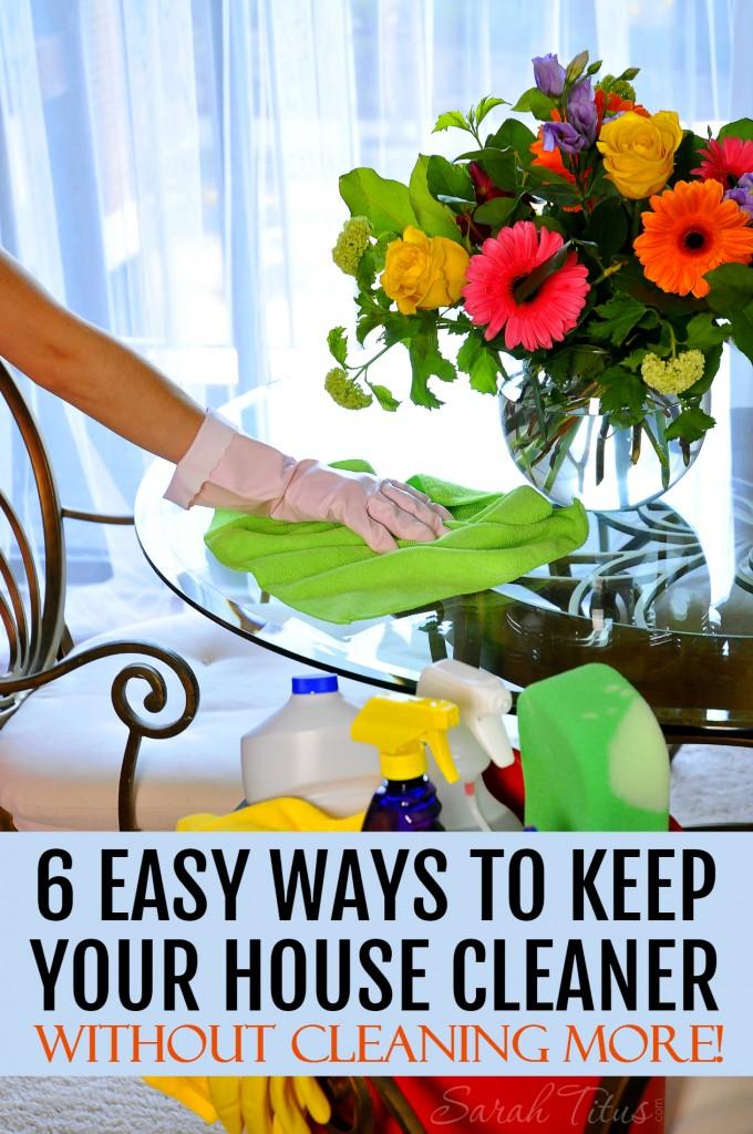 Woman with cleaning gloves on cleaning a glass table with a vase of colorful flowers and a bin of cleaning supplies