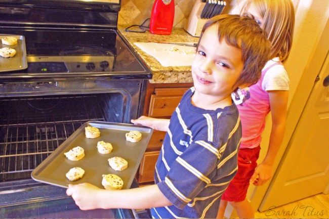 Little boy putting cookies in the oven to bake