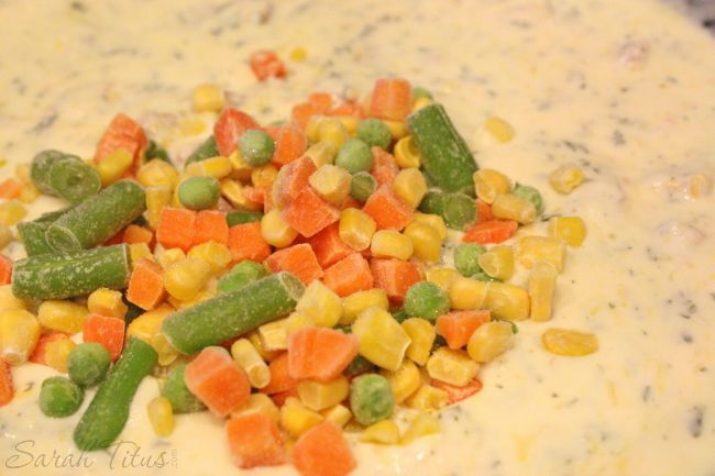 Adding frozen mixed vegetables to sauce mixture in large pan