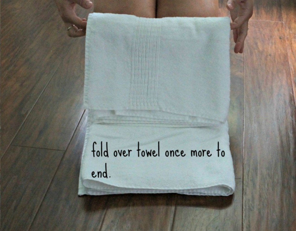 Female holding a towel showing how to fold it