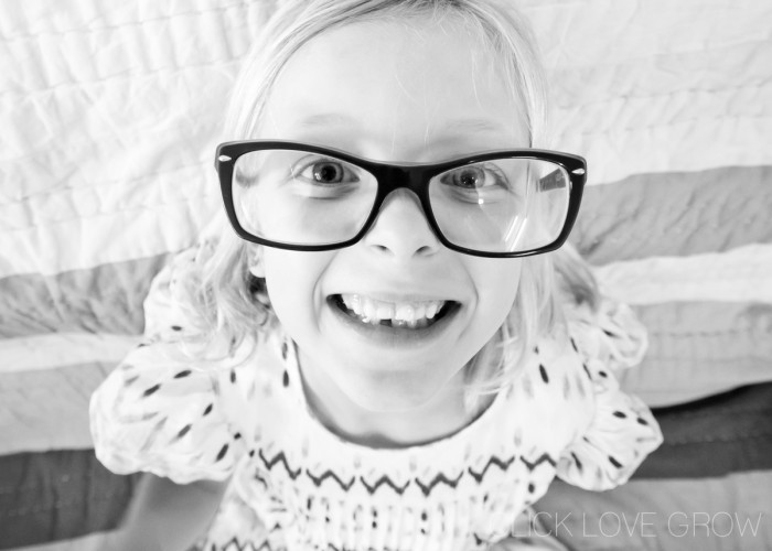 Black and white photo of a smiling girl with big glasses
