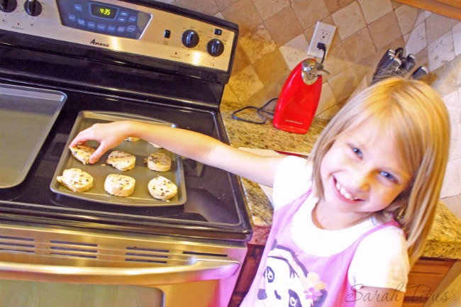 Little girl putting cookie dough on a cookie sheet