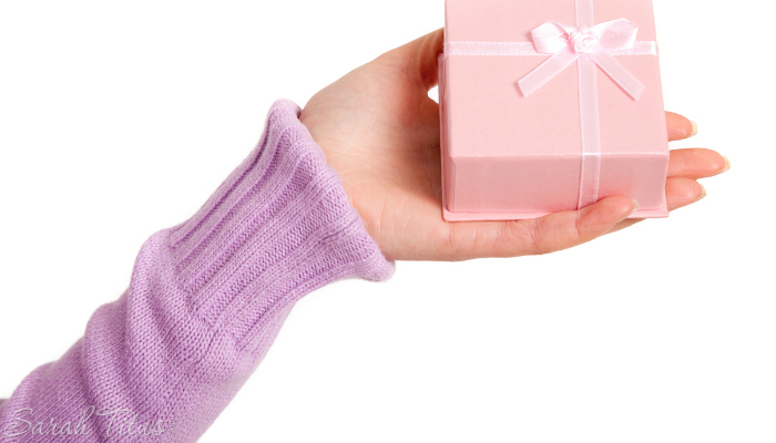 Girl holding a small pink gift box