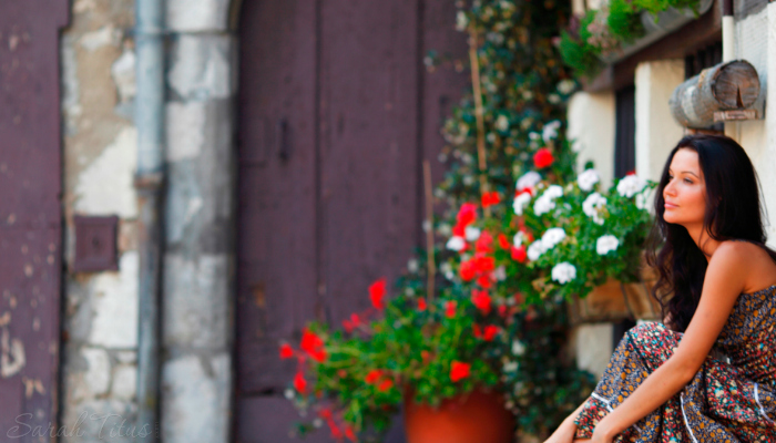 Woman sitting outside on steps next to flowers contemplating how to make it through a huge trial