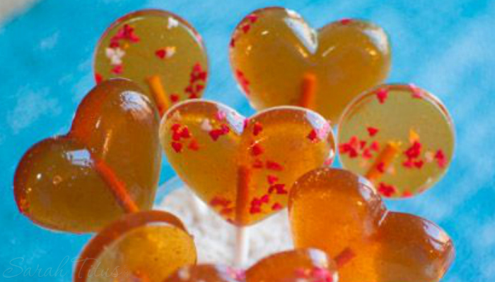 A bunch of yummy gold and red easy honey lollipop on a blue background!