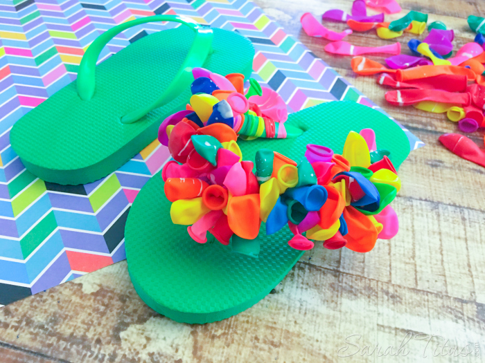 One green flip flop completely finished with colorful balloons tied on to the green straps