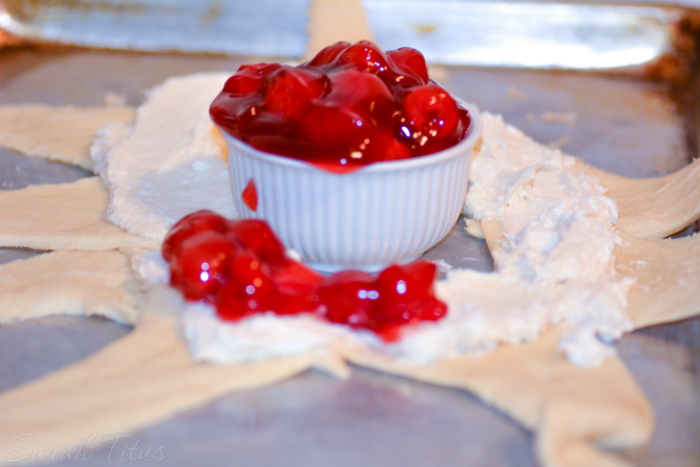 Crescent roll dough spread with cream cheese and a beautiful bowl full of red cherry pie filling