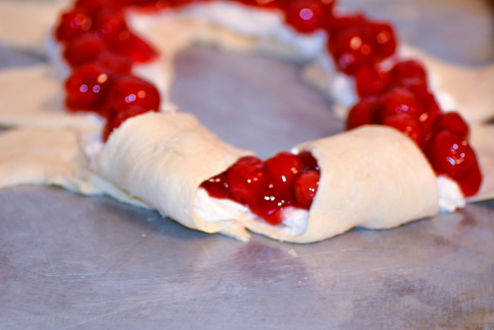The crescent roll dough spread with the cherry pie filling started to be folded over to make the ring
