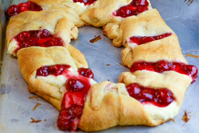 The freshly baked Cherry Cheesecake Crescent Ring on a parchment lined baking sheet