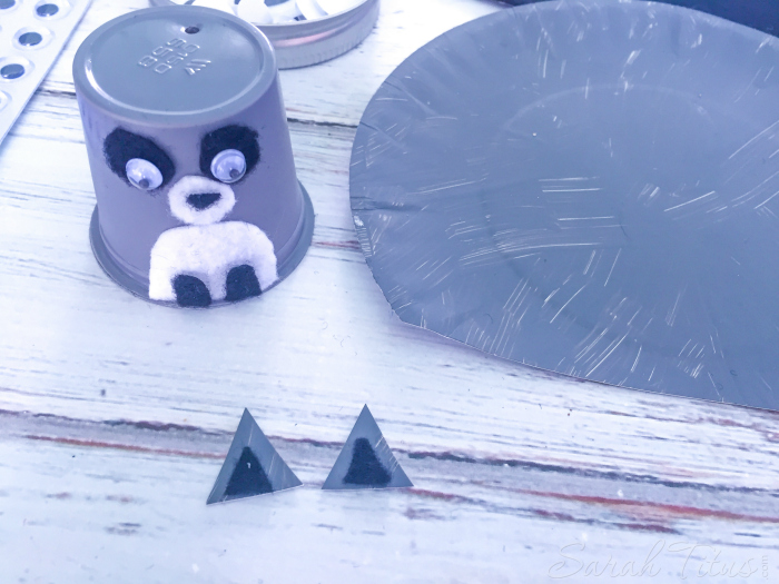 Add eyes and nose onto K cup to make raccoon face and make little raccoon ears
