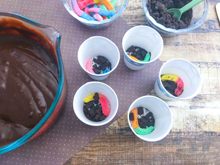 Sprinkling crushed oreo cookies on top of the gummy worm in each Dixie cup