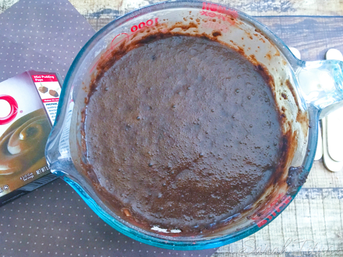 The mixed pudding and milk mixture in a large glass measuring cup
