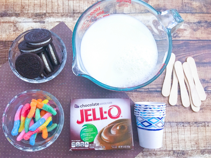Mud Pie Pudding Pops' ingredients of oreo type cookies, milk, chocolate pudding, gummy worms, Dixie cups and ice cream spoons