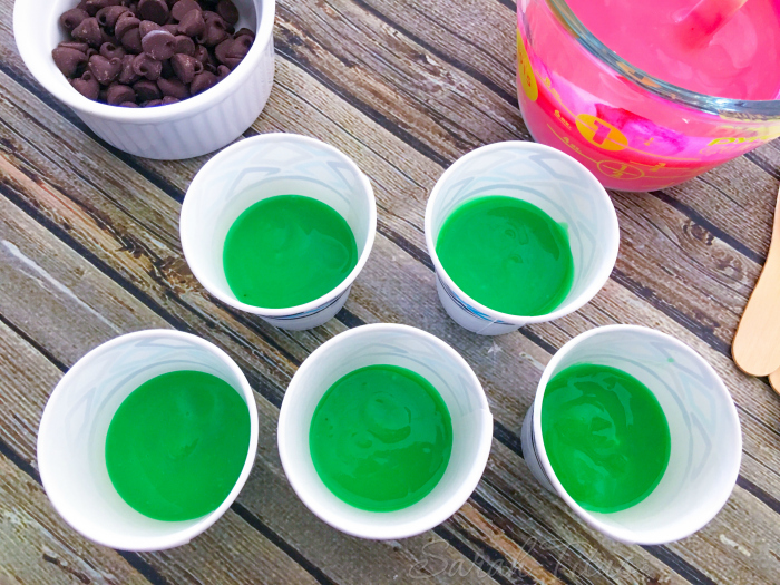 Dixie cups with green colored pudding in the bottom sitting next to chocolate chips and pink colored pudding