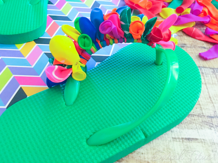 Continuing to tie colorful balloons on to the green flip flop straps for the Balloon Flip Flops