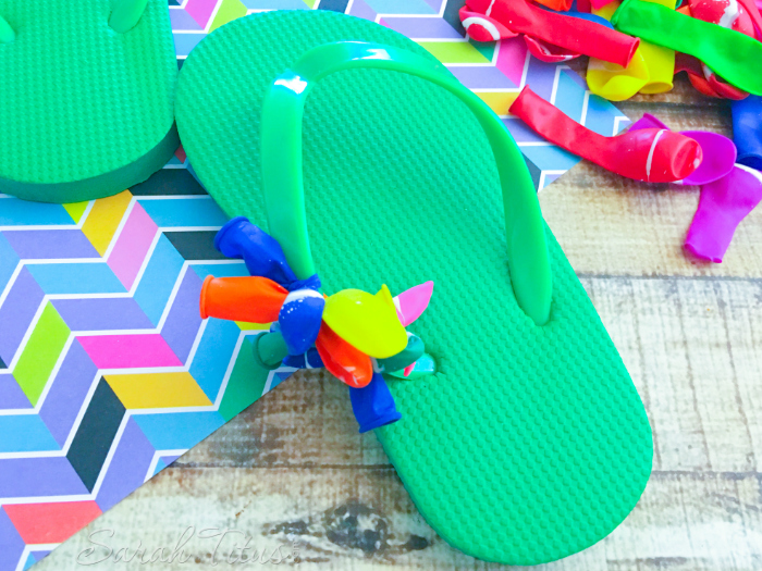 Starting the Balloon Flip Flops craft by tying balloons onto the straps
