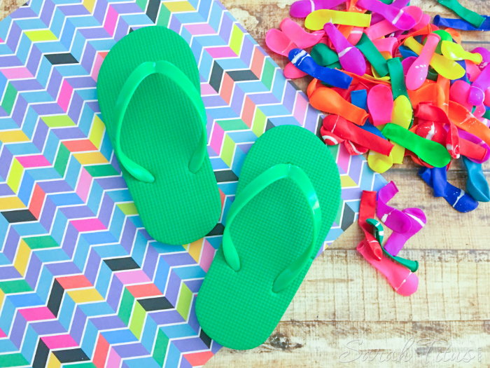 Green child's flip flops on a wooden table with a pile of all different colored balloons in a pile on the side
