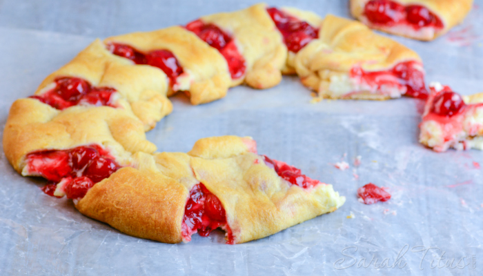 Scrumptious looking Cherry Cheesecake Crescent Ring on a parchment lined baking sheet