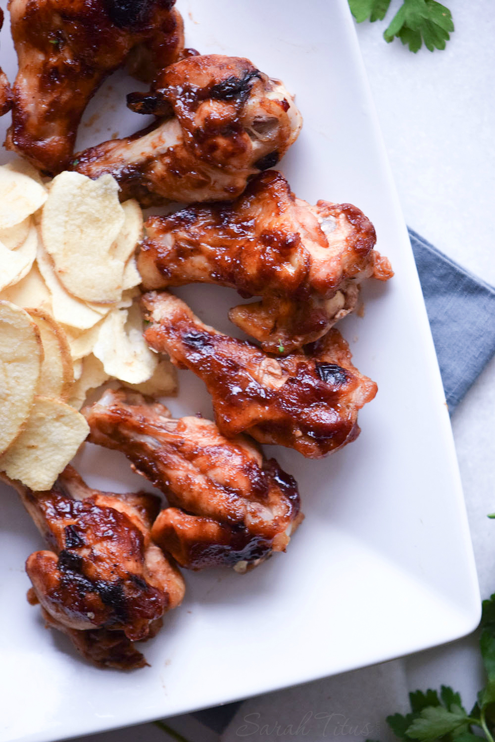 Fully cooked Sweet and Spicy Chicken Wings on a white plate with a side of potato chips all sitting on a blue cloth