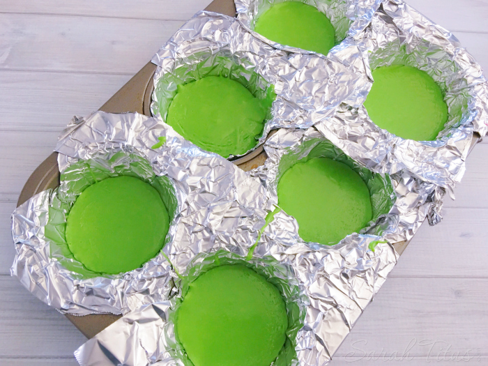 Green melting candy mixture poured into foil lined muffin mold tin