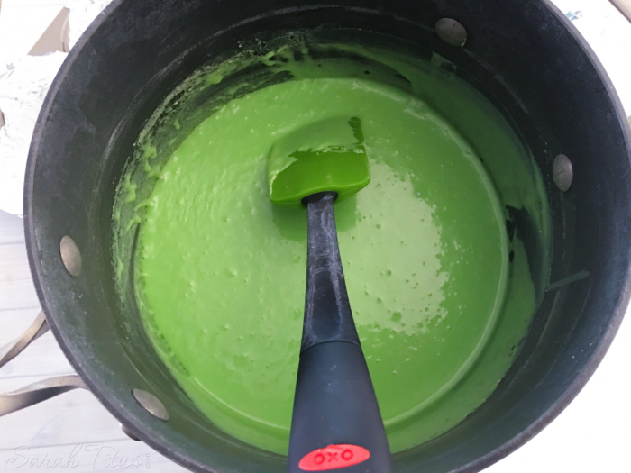 Stirring green melting candy, vanilla and milk in a saucepan