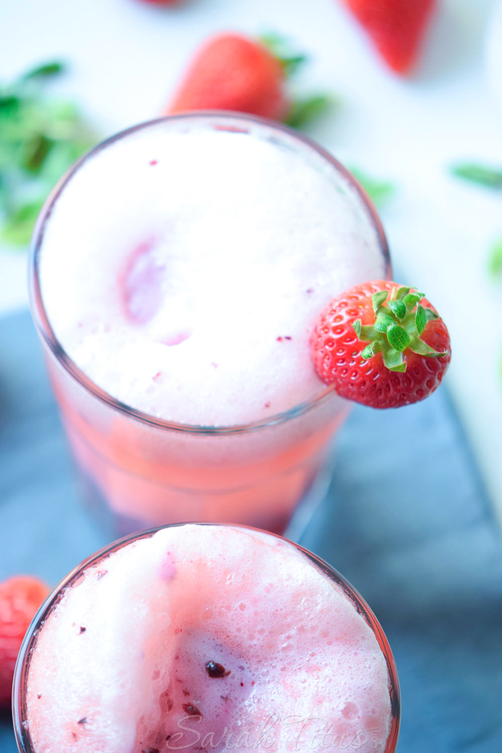 Topping the Very Berry Ice Cream Float with more ice cream and garnished with a fresh strawberry