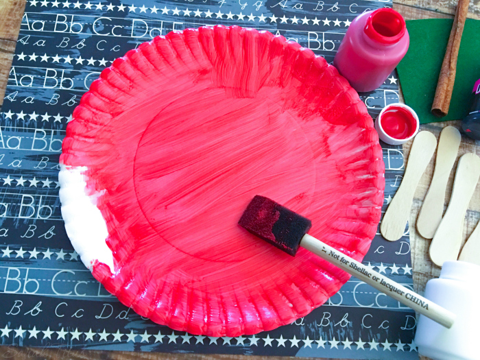 Painting paper plate red for the Paper Plate Apple {Kids Craft}