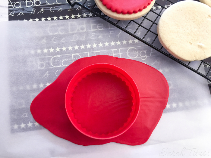 Cutting red fondant with fluted round cookie cutter to place on top of baked cookies