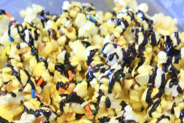 Finished Birthday Cake Popcorn which is drizzled with chocolate syrup and sprinkles