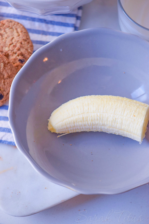 Half of a banana in a blue bowl with chocolate chip cookies and milk on the side