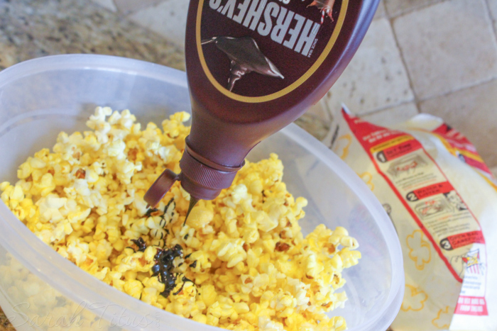 Drizzling chocolate syrup over popcorn in a large plastic bowl