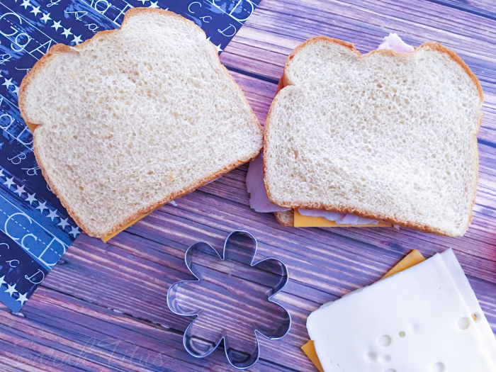 Bread, turkey and cheese laid on a cutting board with a flower shaped cookie cutter and alphabet napkin