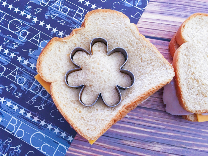 Cutting turkey and cheese sandwich with the flower shaped cookie cutter for the Flower Bento Box
