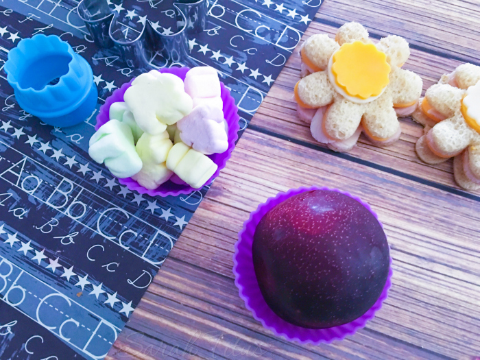 The Flower Bento Box food items: turkey and cheese flower shaped sandwiches, a plum and colorful marshmallows