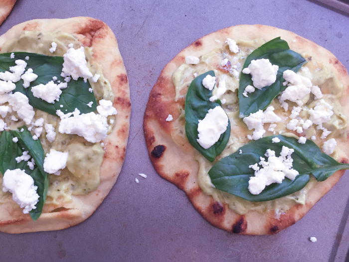 Sprinkling the Feta cheese on top of the basil leaves, pesto and Naan bread