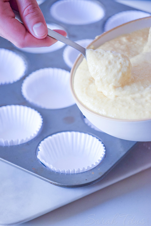 Nutella Swirl Muffins batter being scooped into a metal muffin tin lined with white cupcake papers