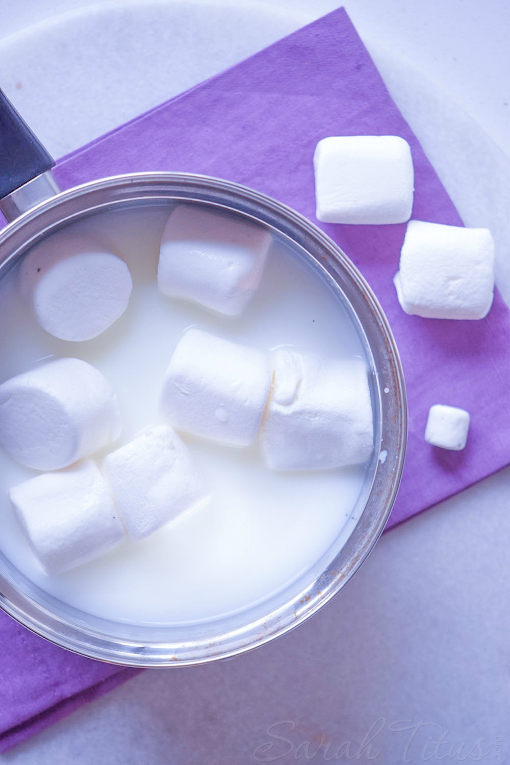 Milk and marshmallows melting in a saucepan with marshmallows on the side on a purple cloth napkin