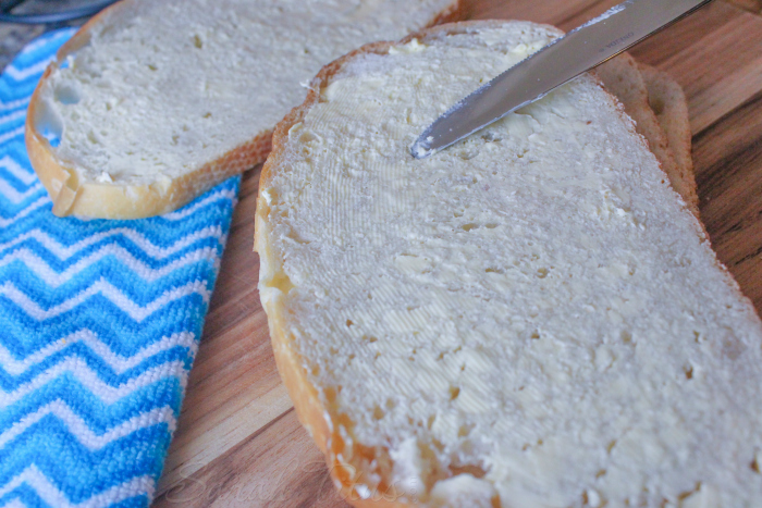 Spreading butter on sourdough bread on a wooden cutting board with blue striped cloth