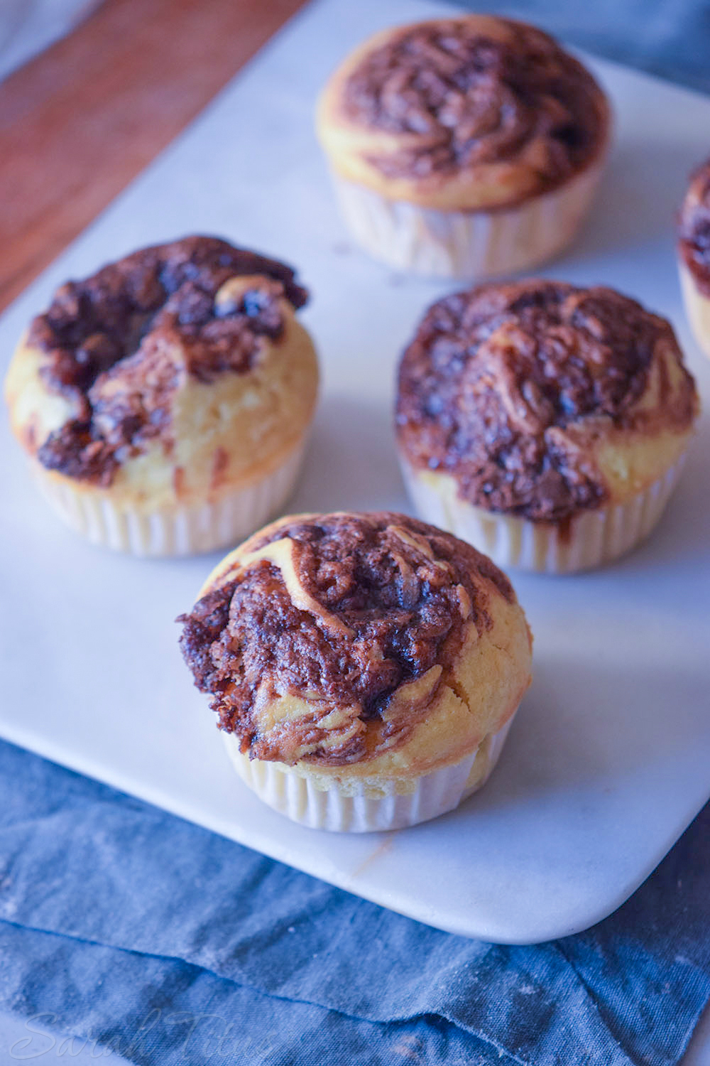 Freshly baked Nutella Swirl Muffins on a white cutting board on a blue cloth and wood table
