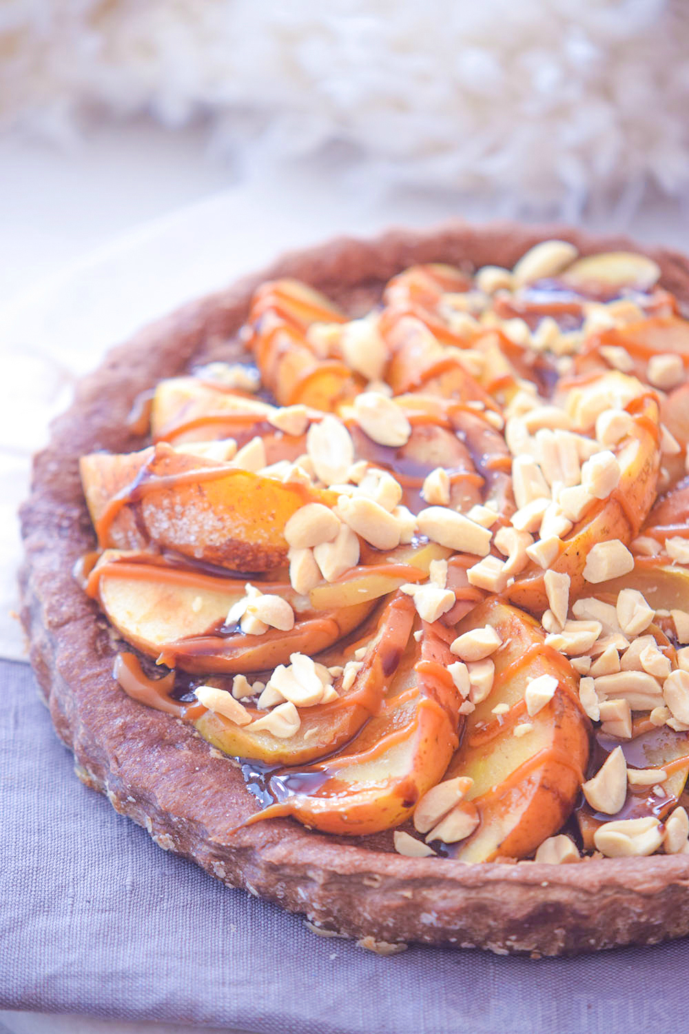 The finished Caramel Delight Apple Pie with a combination of caramel apples and topped with sliced almonds and drizzled caramel