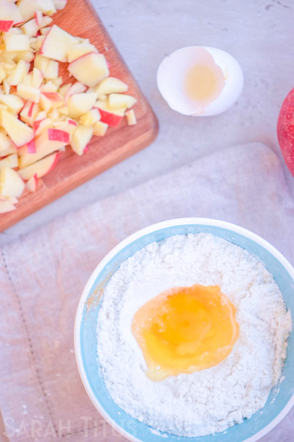 Adding an egg to the dry ingredients bowl for the baked apple doughnuts